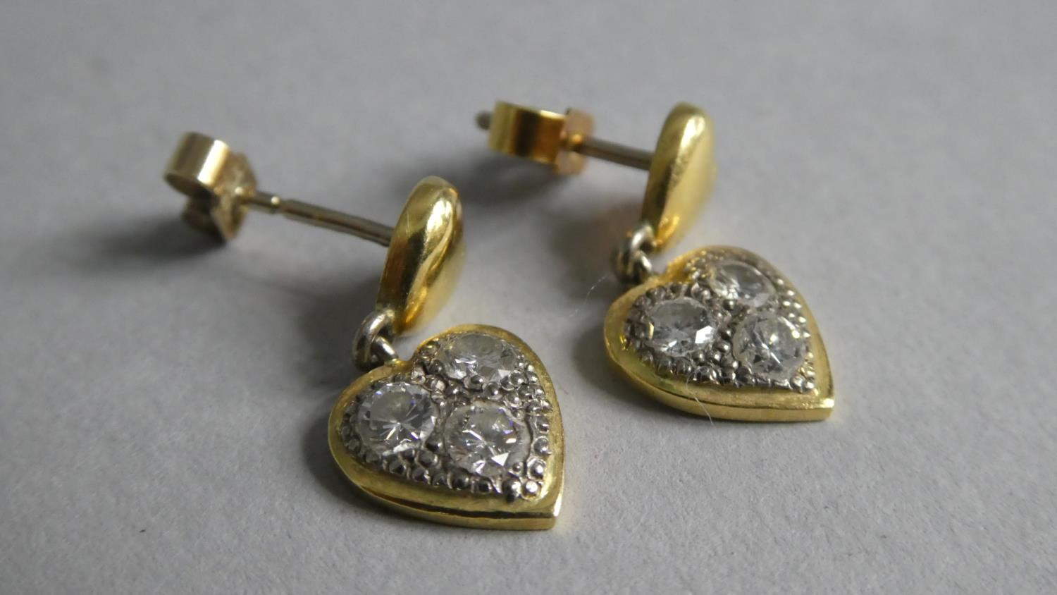 Lot 335 - A Pair of 18ct Yellow Gold and Diamond Earrings. Heart Shaped Drops containing Three Diamonds.
