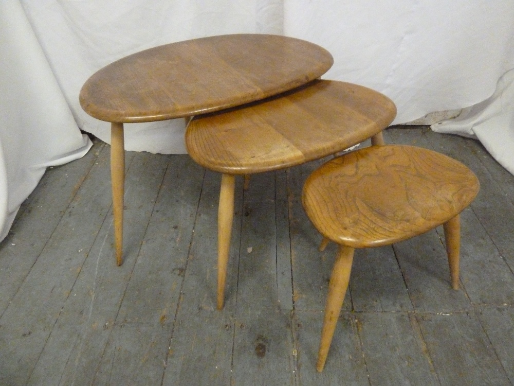 Lot 23 - Ercol nest of three tables of oval form with spindle legs, label to base