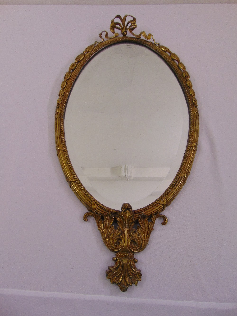Lot 49 - An oval neo-classical style gilded metal bevelled edge wall mirror