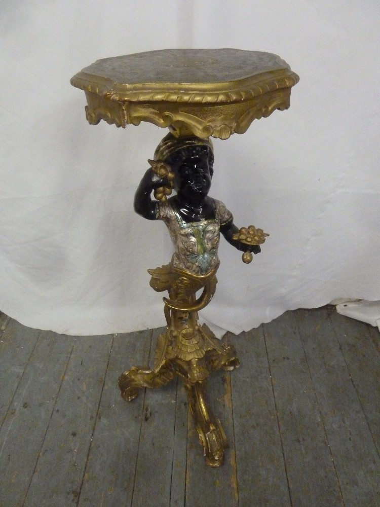 Lot 28 - A carved wooden Blackamoor plant stand supporting a shaped circular top on three scroll supports,