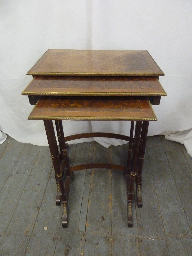 Lot 22 - A nest of three inlaid rectangular side tables, gilded metal borders
