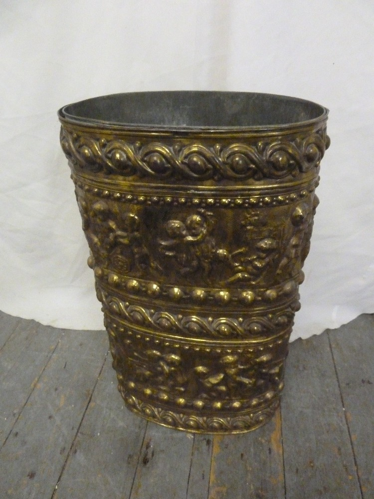 Lot 46 - A shaped oval brass umbrella stand the side embossed with flowers, leaves and scrolls to include