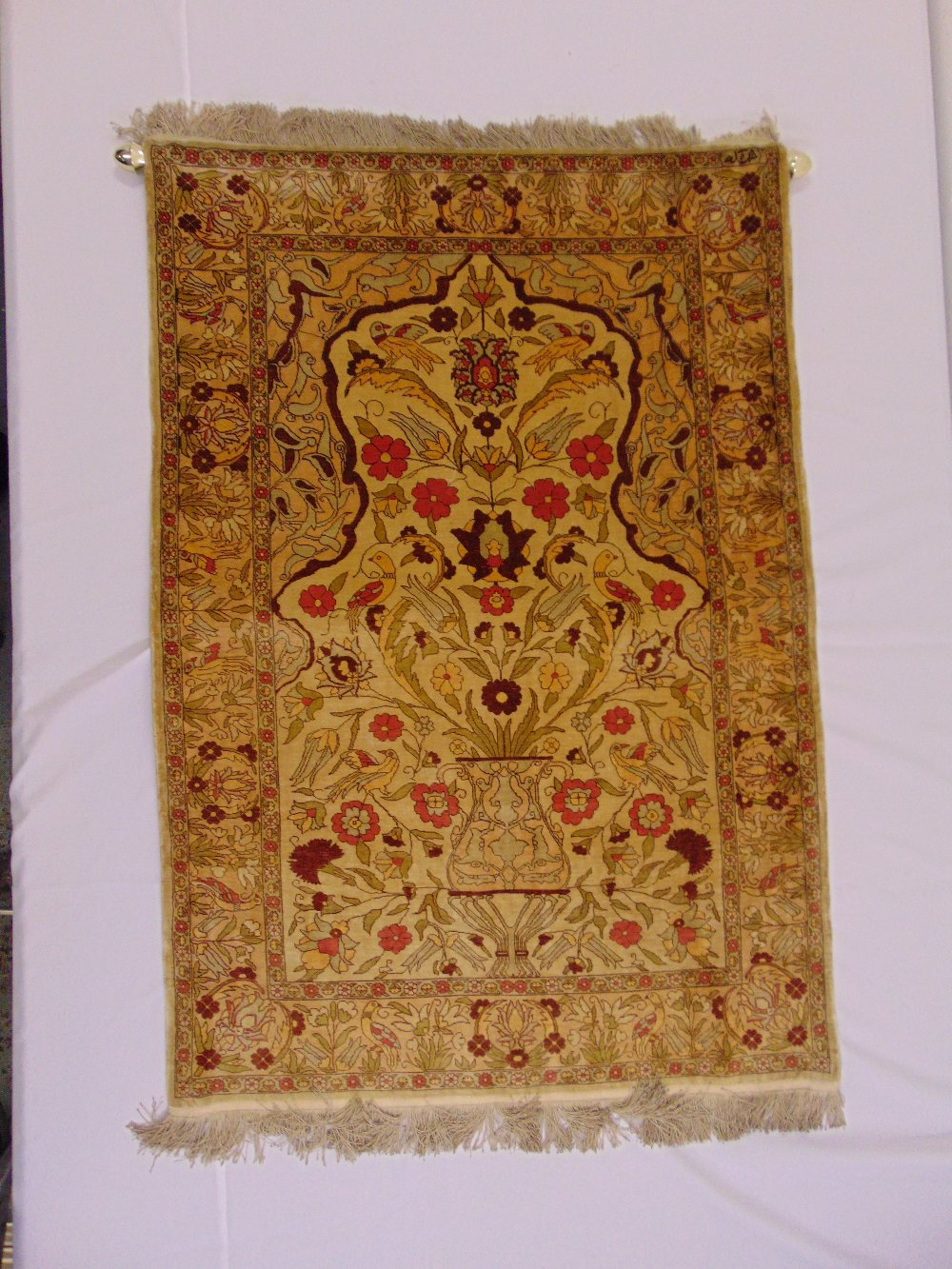 Lot 51 - A Persian silk rectangular wall hanging decorated with flowers and leaves against a tan border, 113x