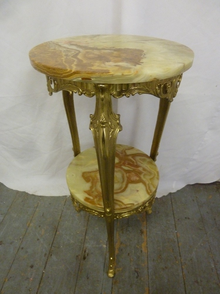 Lot 25 - An onyx and gilded metal circular side table on three scroll supports