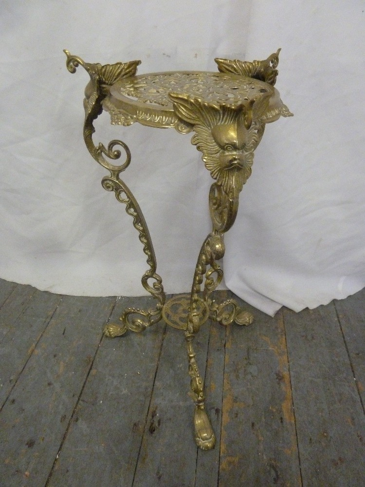Lot 26 - A brass plant stand on three outswept legs decorated with scrolls, leaves and flowers