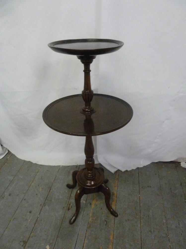 Lot 21 - A mahogany circular tea table on four scroll legs