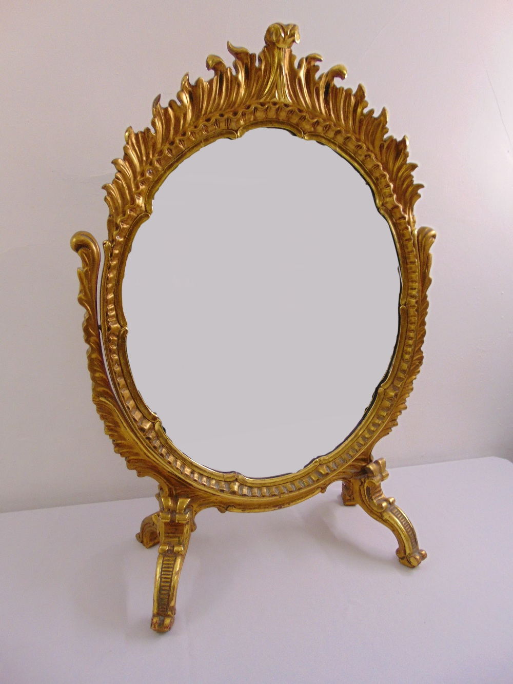 Lot 48 - An oval gilded wood heavily carved tilt top dressing table mirror on four scroll legs