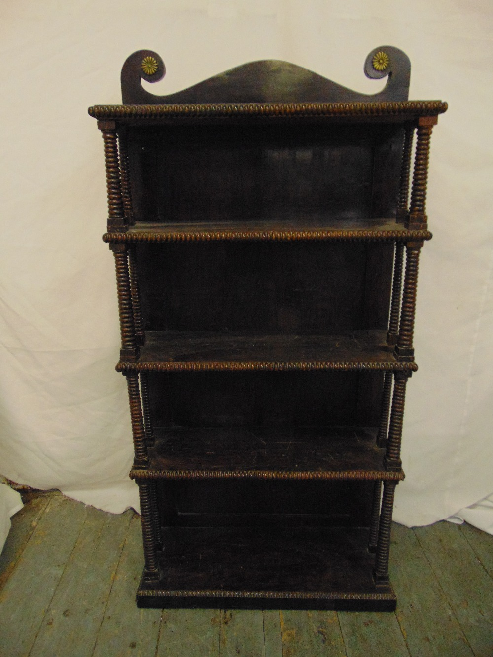 Lot 25 - A mahogany rectangular five tier whatnot with turned column supports, swan neck pediment on