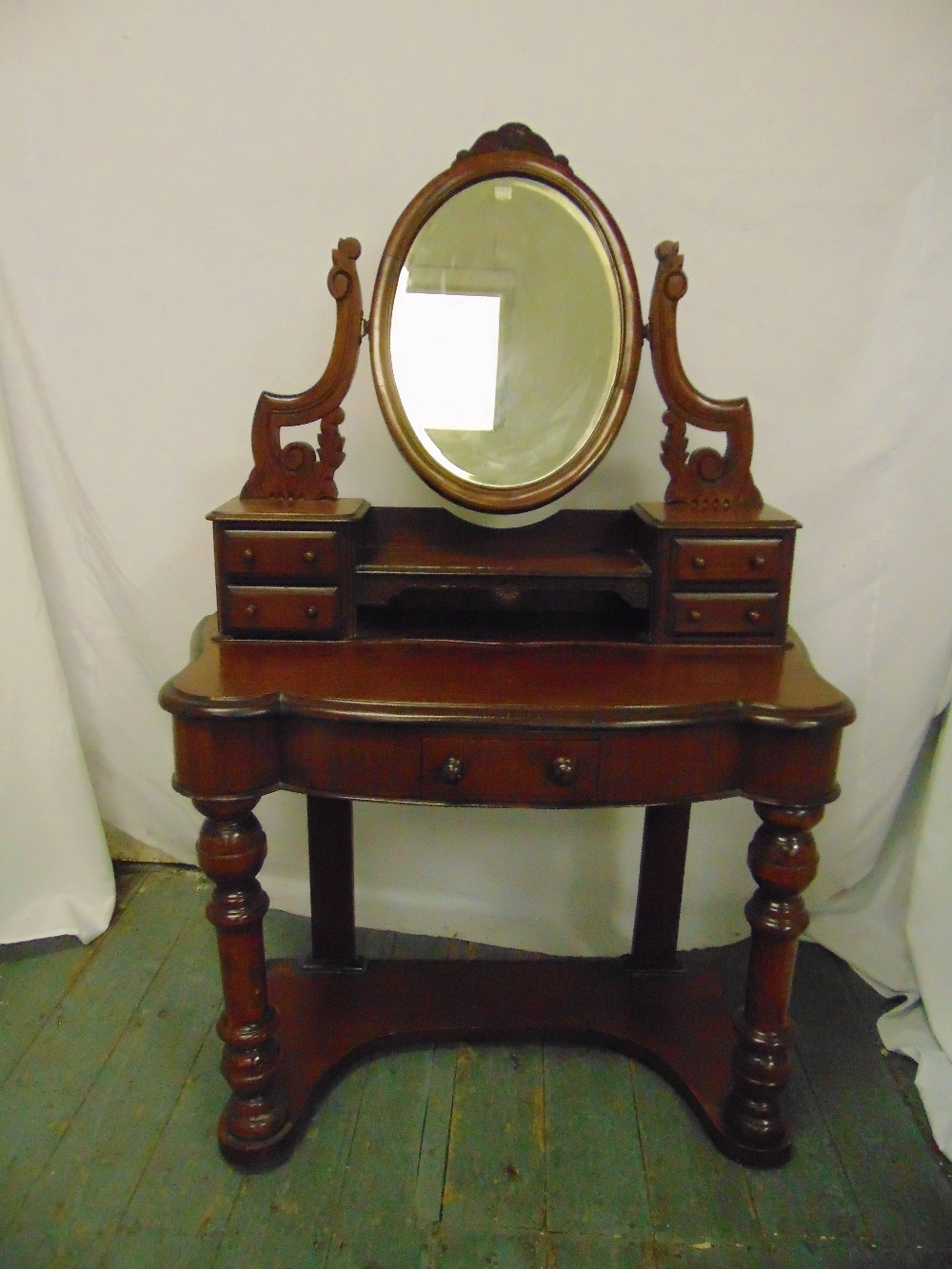 Lot 13 - A Victorian mahogany shaped rectangular dressing table with oval swivel mirror above five drawers on