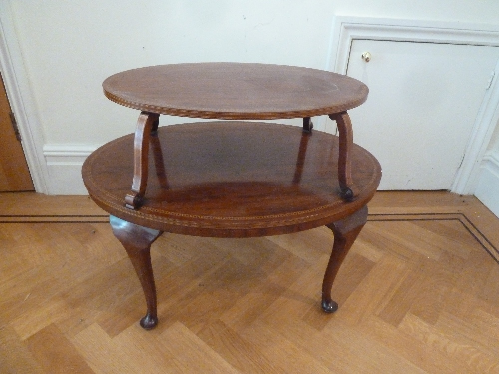 Lot 28 - An Edwardian oval two tier mahogany tea table on cabriole legs