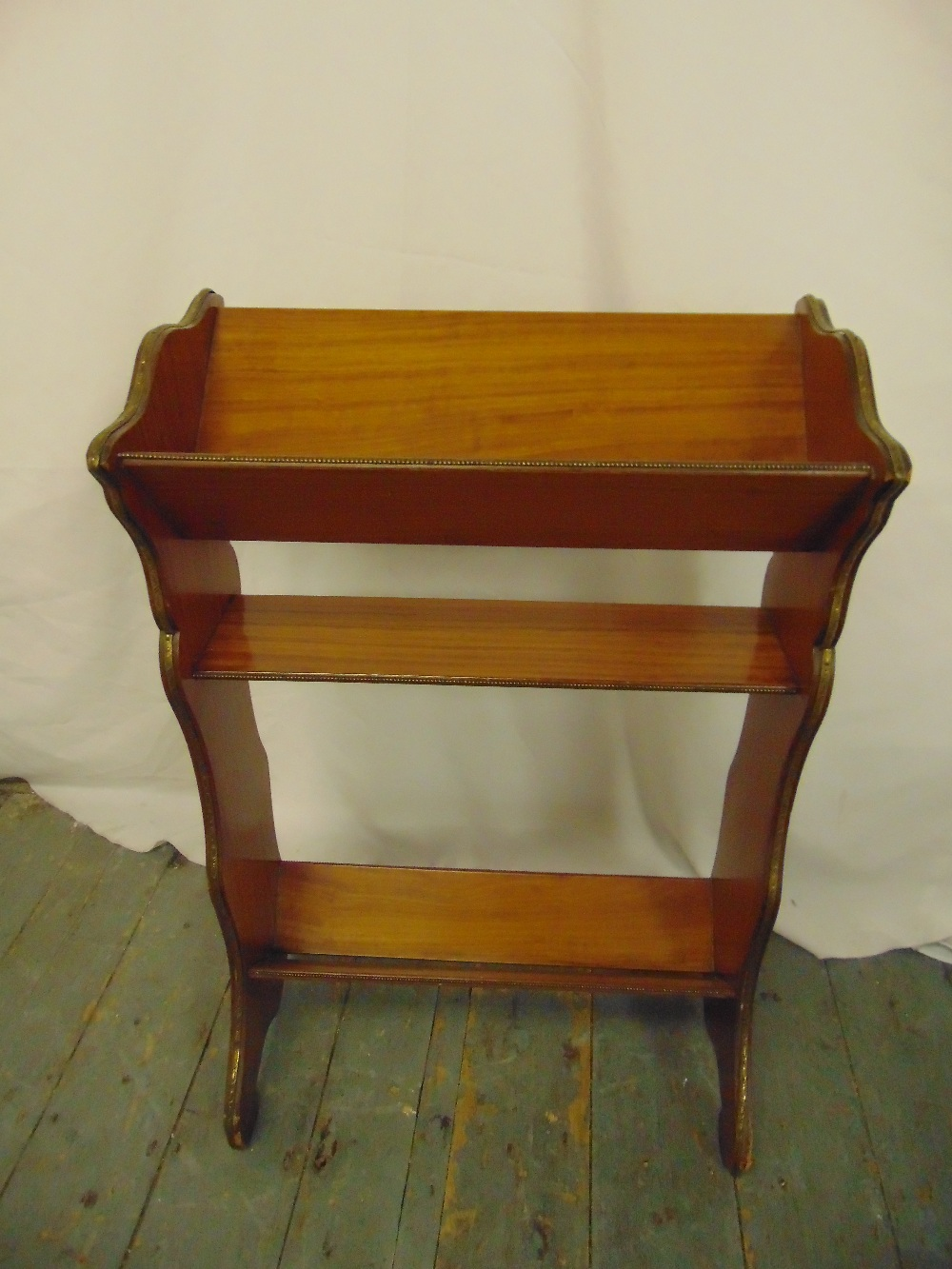 Lot 24 - A mahogany rectangular book stand with gilded metal mounts on four scroll legs