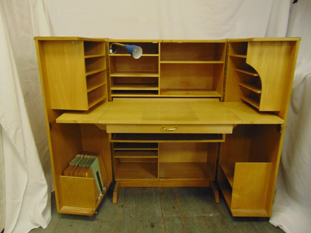 Lot 4 - A 1960s light oak rectangular desk cum cupboard, the hinged doors revealing book and stationery