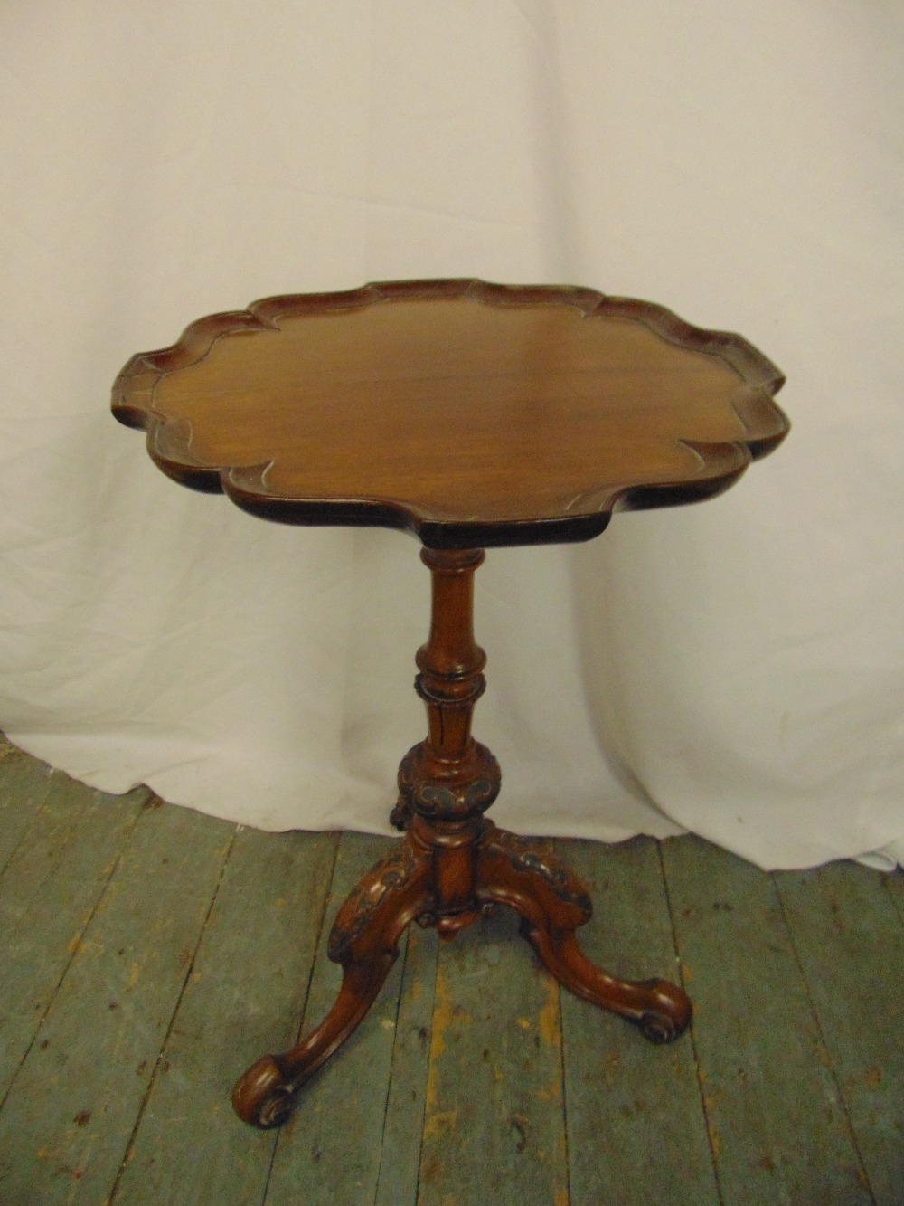 Lot 29 - A mahogany wine table, shaped circular top with Chippendale style border on three scroll legs
