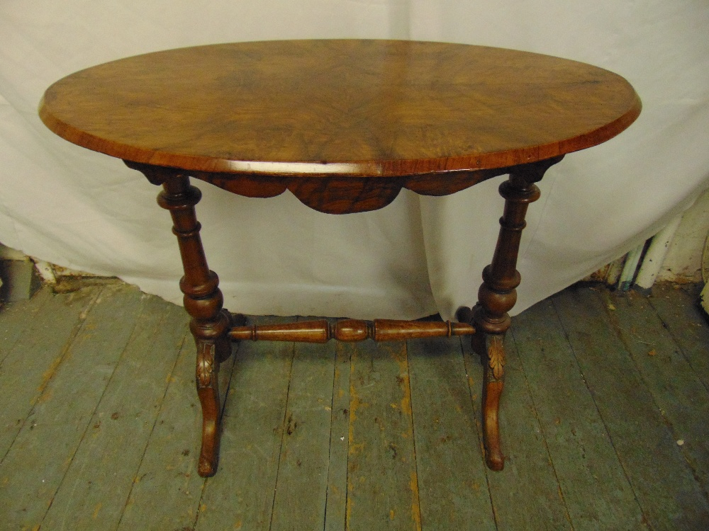 Lot 21 - A Victorian walnut and mahogany oval occasional table on turned columns and outswept legs