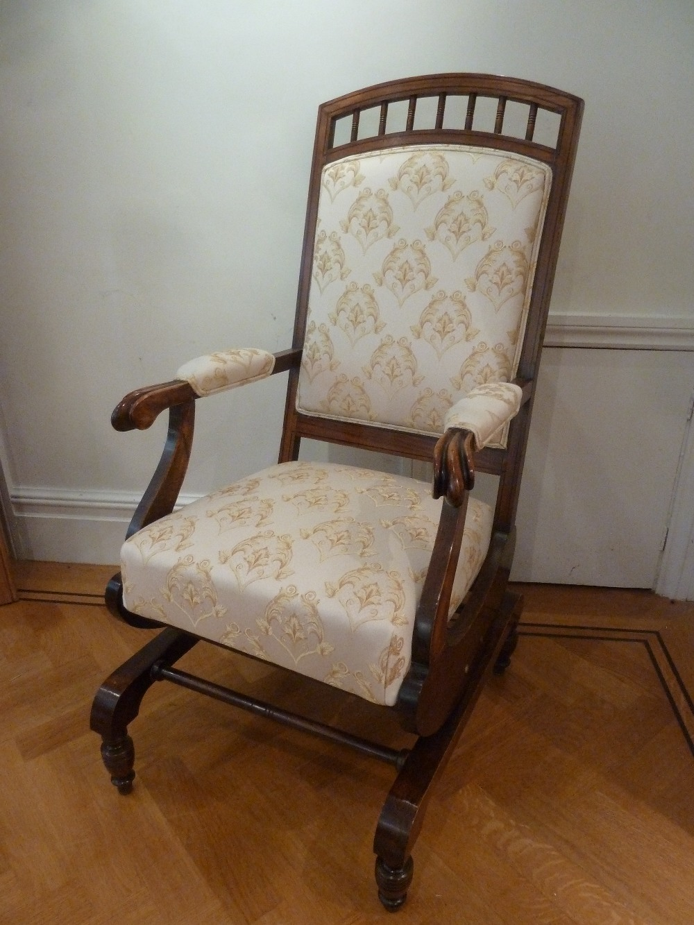 Lot 45 - An Edwardian mahogany upholstered rocking chair on four turned supports