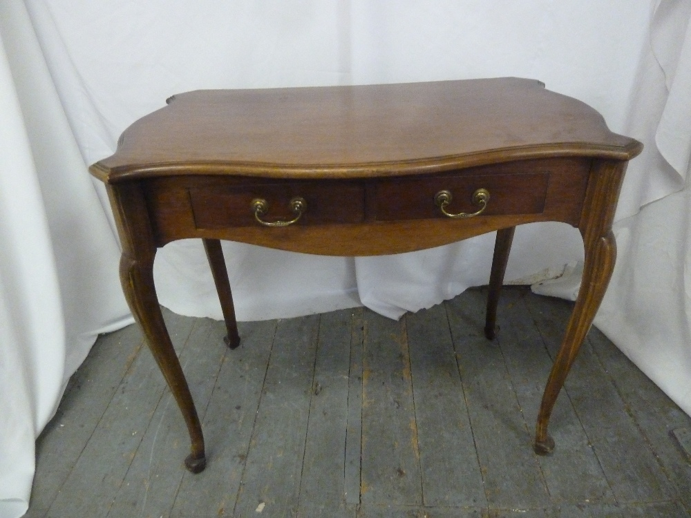 Lot 8 - A rectangular mahogany desk with two drawers and brass swing handles on four cabriole legs