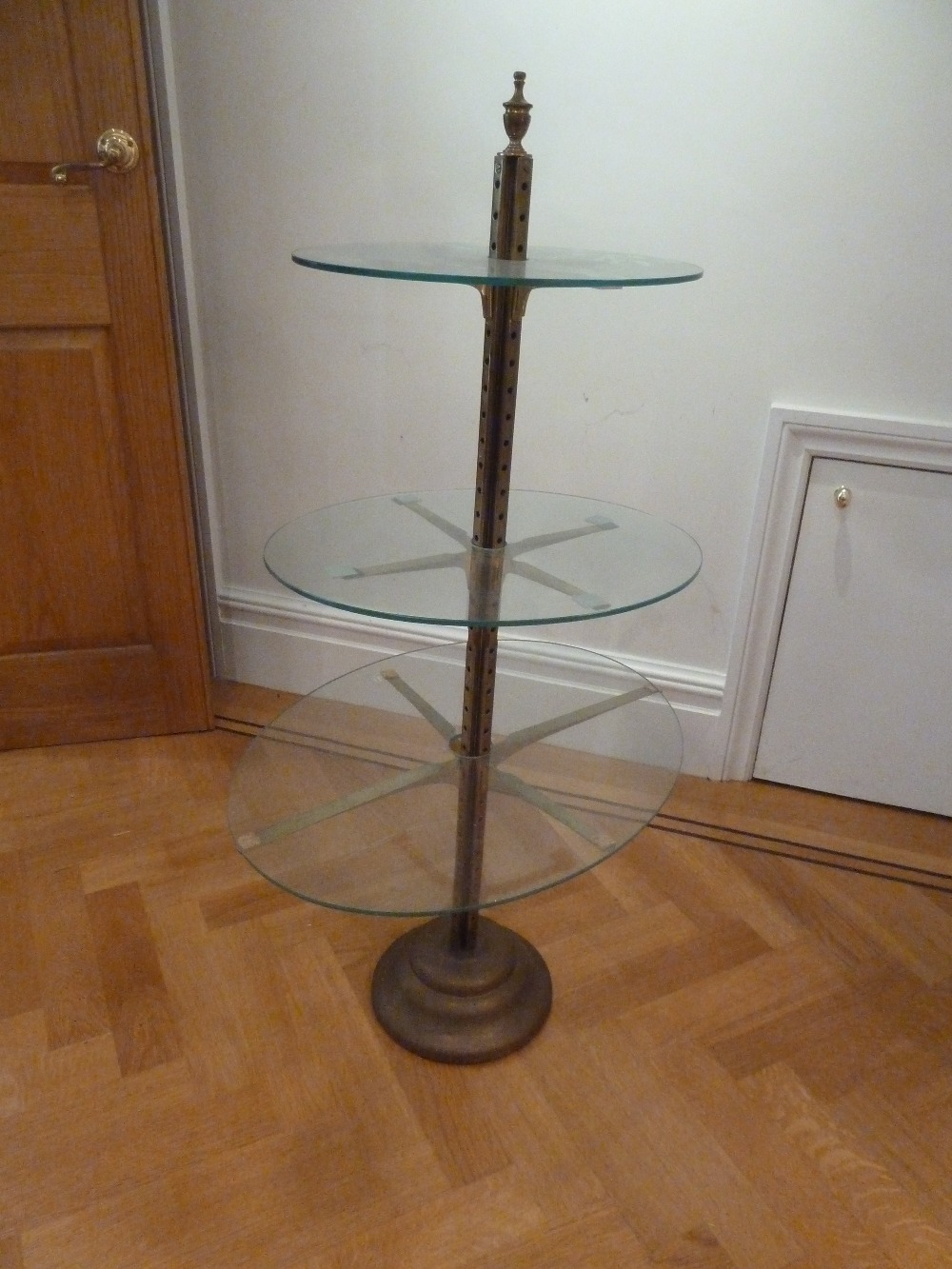 Lot 37 - A brass and glass three tier stand with urn finial on raised circular base