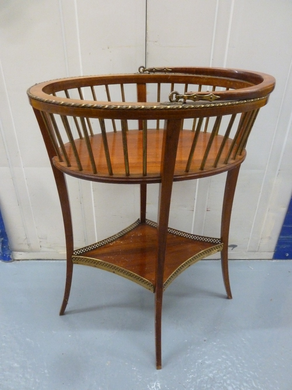Lot 38 - An oval wooden plant stand with slatted sides, swing handle on four cabriole legs