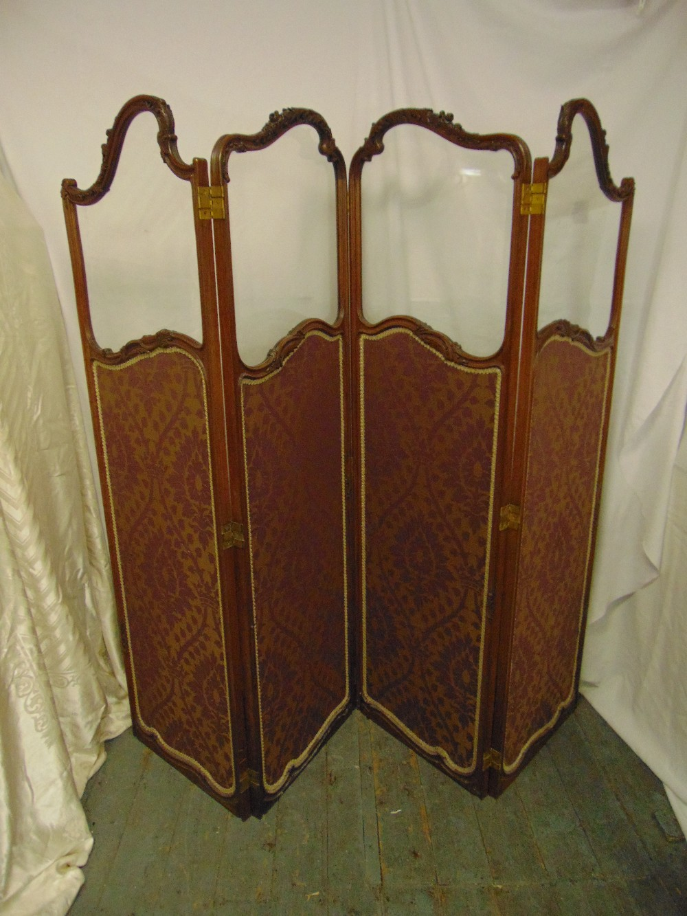 Lot 16 - A French mahogany and glazed four panel screen decorated with material panels with stylised leaf and