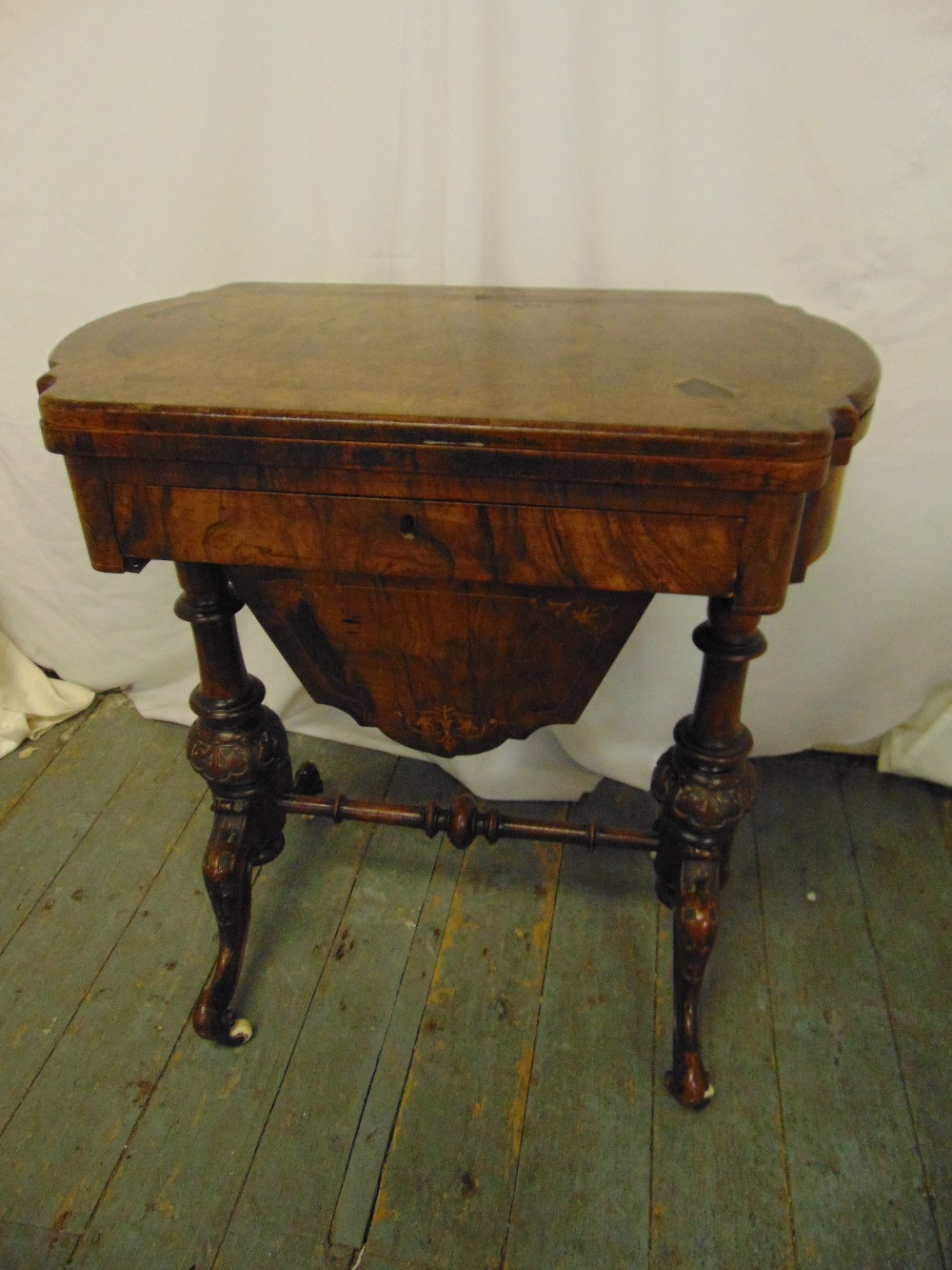 Lot 2 - A 19th century walnut and mahogany games and sewing table of shaped rectangular form on four knopped