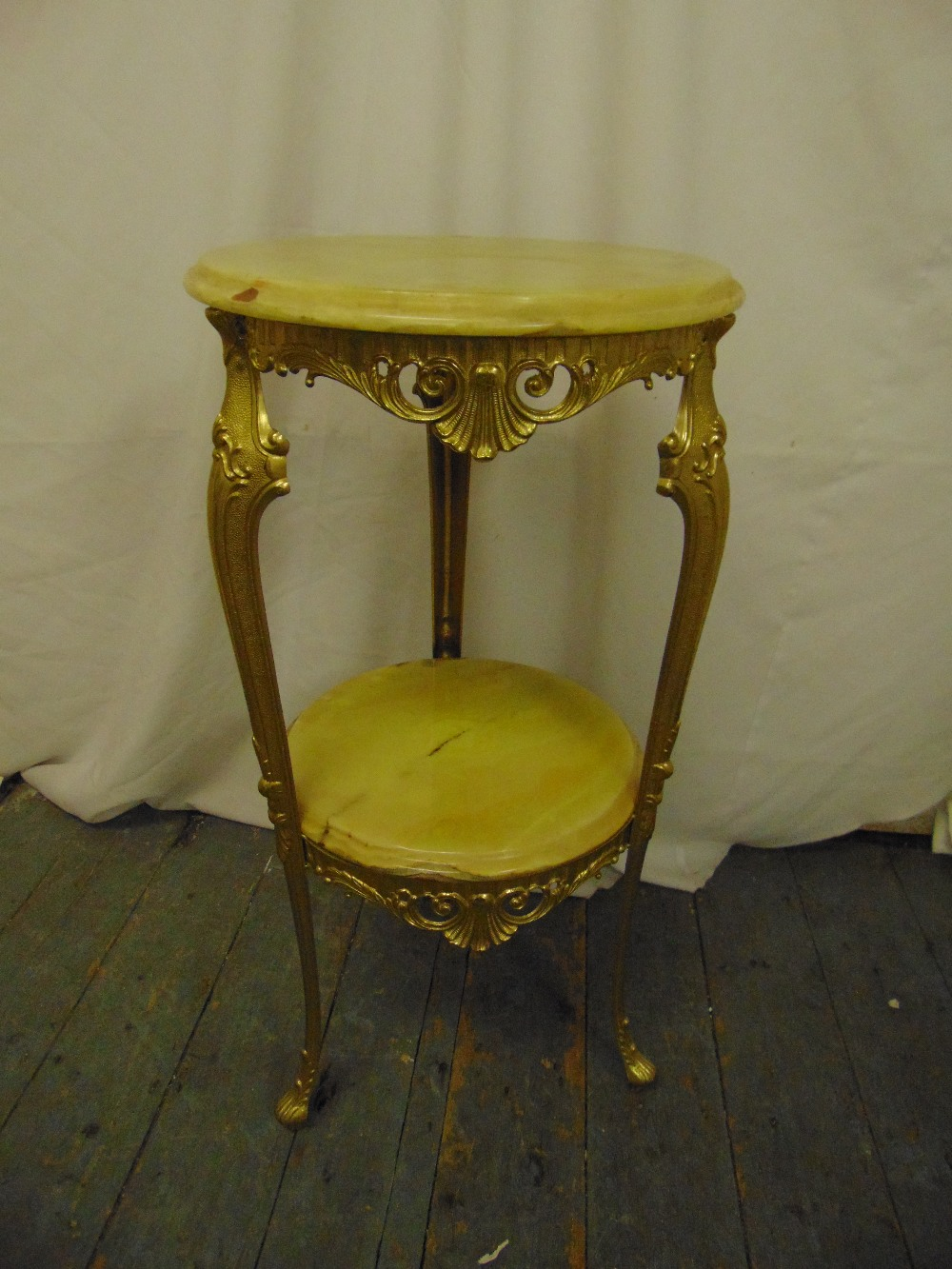 Lot 11 - An onyx and gilded metal side table, circular with scrolling supports