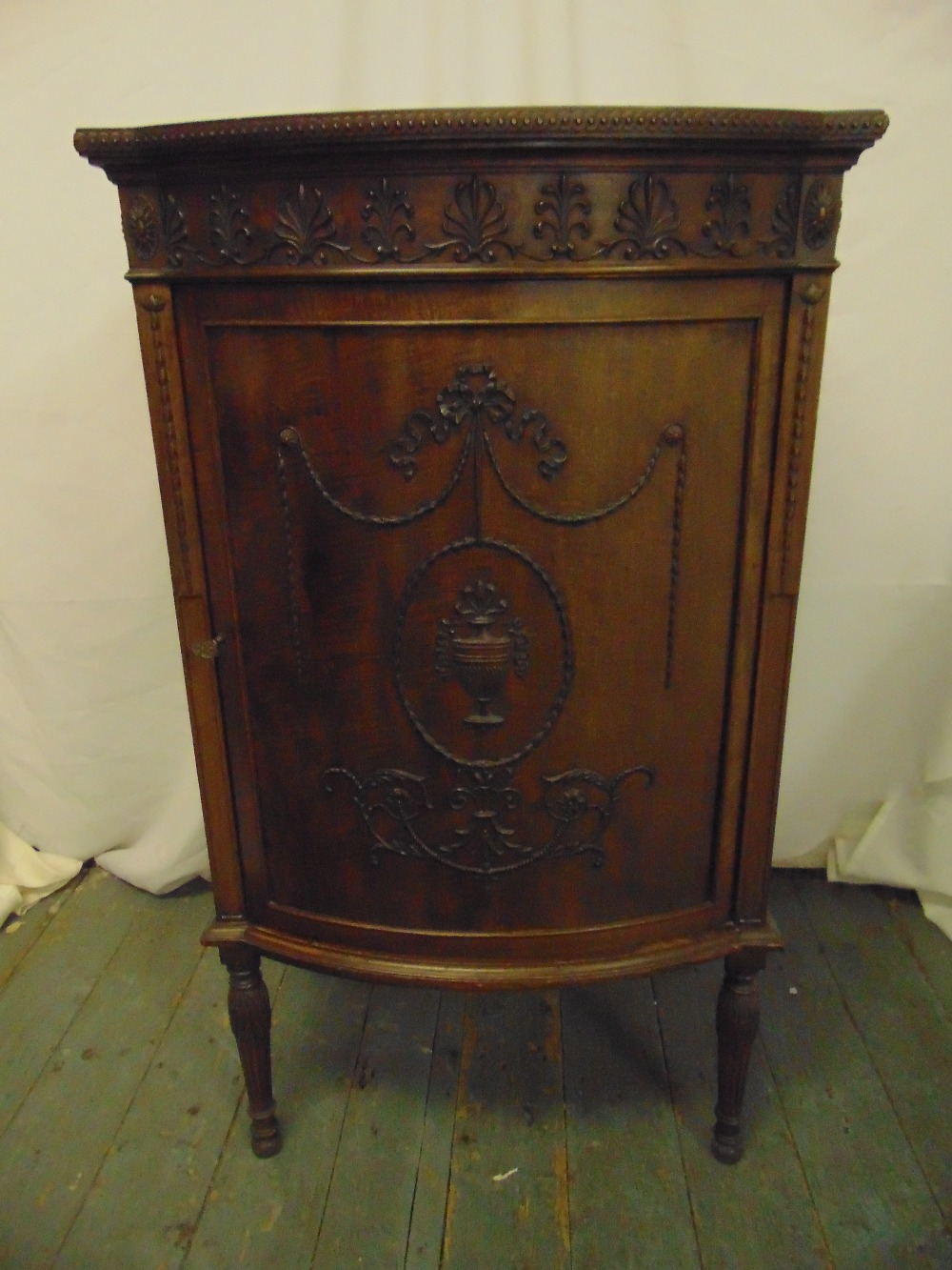 Lot 4 - A shaped rectangular mahogany music cabinet, bow front with anthemion border, the hinged door with