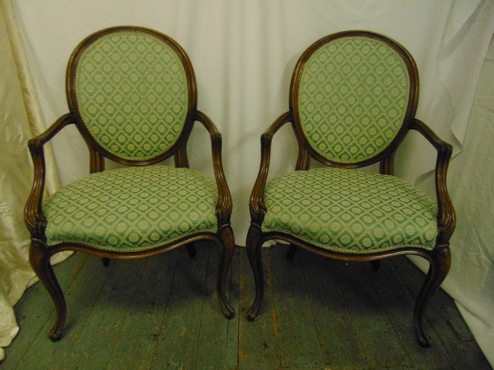 Lot 17 - A pair of French upholstered mahogany armchairs, oval backs, scroll arms and legs