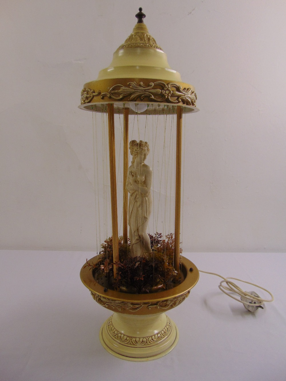 Lot 24 - A decorative oil lamp in the form of a classical maiden framed by a domed cover and circular base