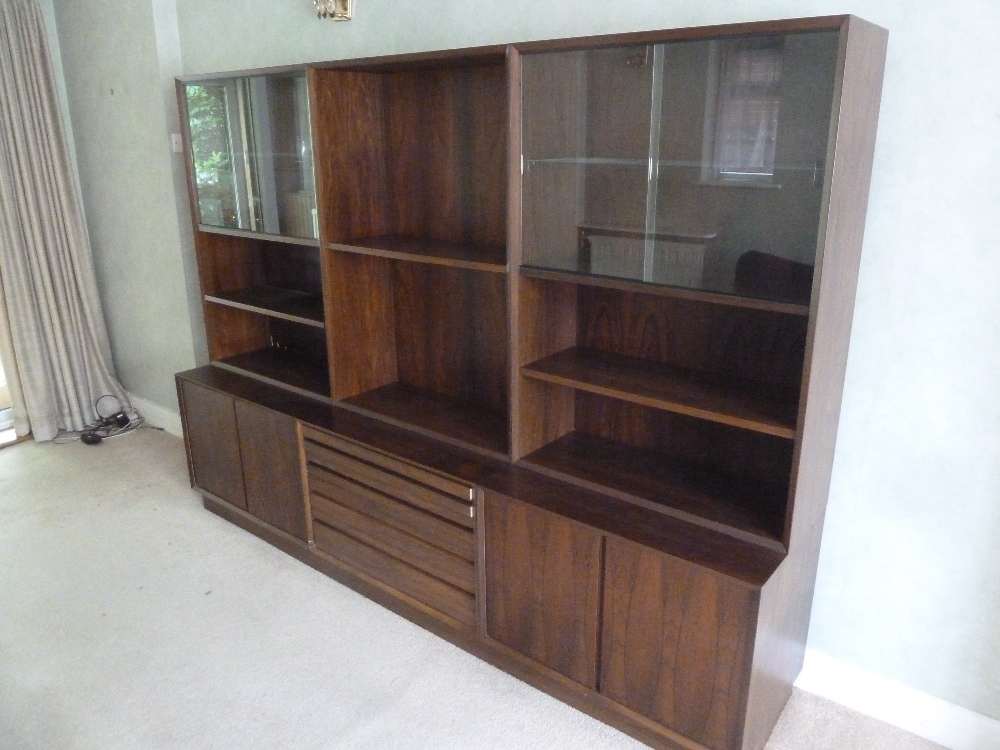 Lot 9 - Danish rosewood rectangular three section wall unit with cupboards and drawers on plinth base, to