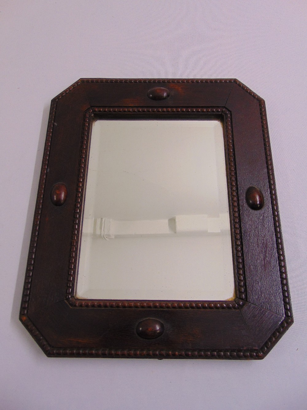 Lot 43 - A mahogany framed Arts and Crafts shaped rectangular bevelled edge wall mirror