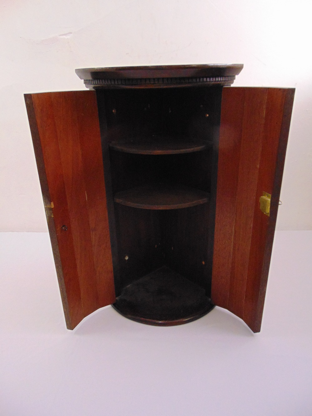 Lot 25 - A mahogany wall hanging corner cabinet with brass hinges and escutcheon