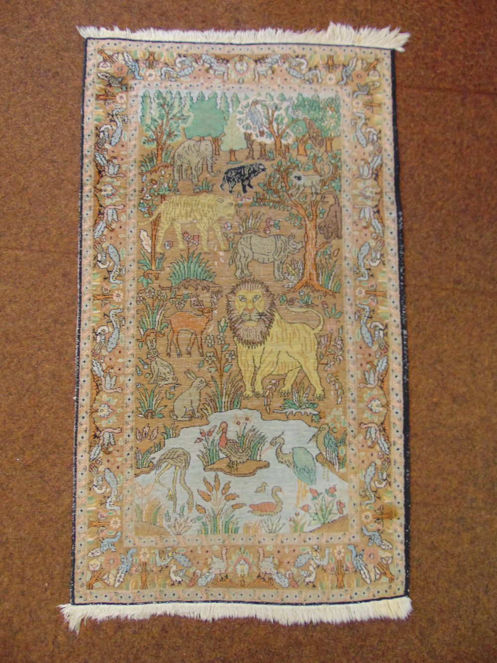 Lot 49 - A Persian carpet depicting stylised wild animals within a border of stylised birds, 131.5 x 76.5cm