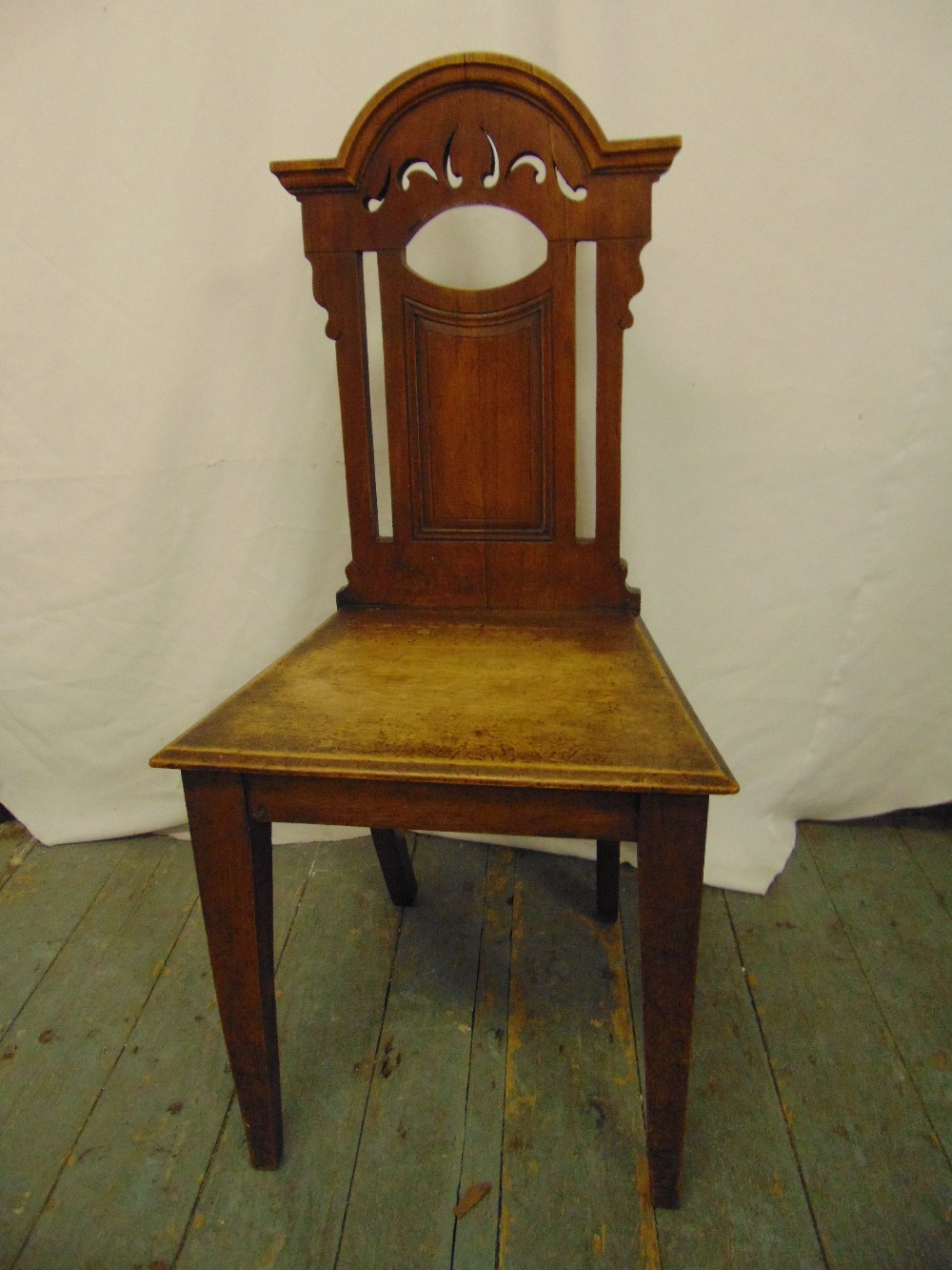 Lot 34 - A 19th century mahogany hall chair with pierced architectural back on four tapering rectangular