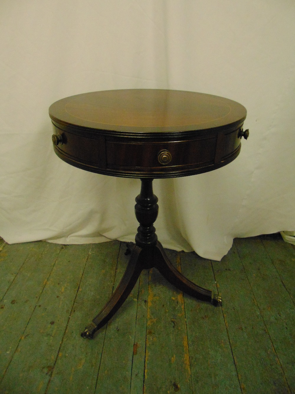 Lot 24 - A mahogany circular drum top table with two drawers on three outswept legs with brass castors