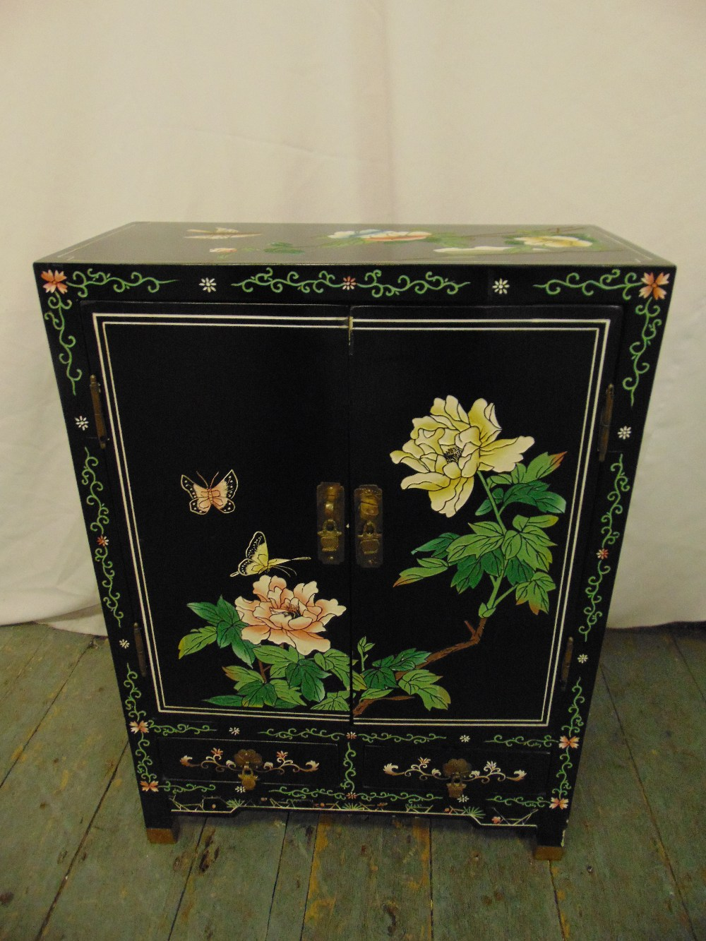 Lot 15 - A Chinese rectangular black ebonised cabinet decorated with butterflies, flowers and leaves