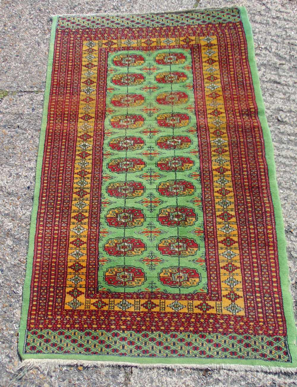 Lot 47 - A Persian wool carpet green ground with repeating motif design, predominately red and green border