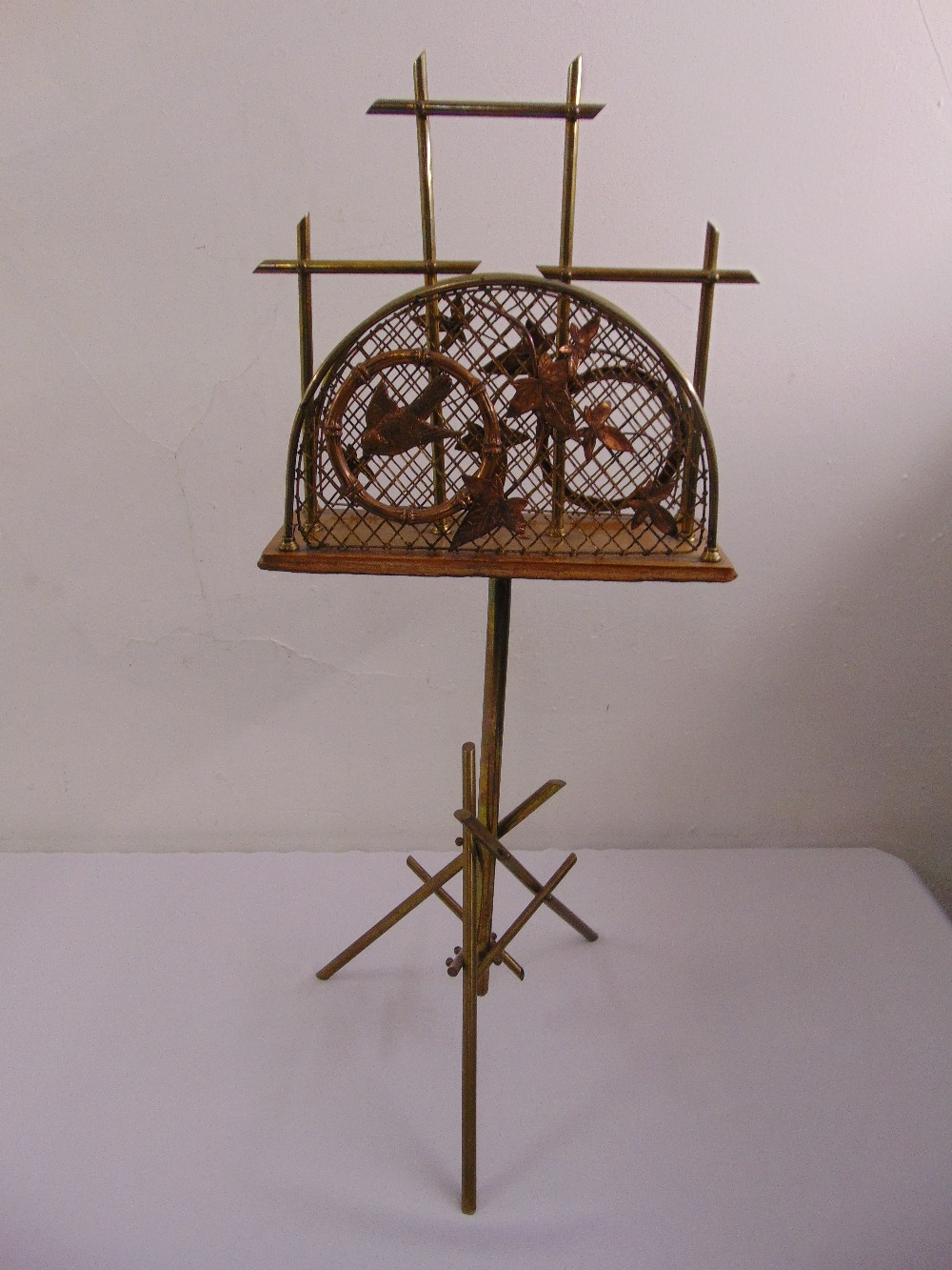 Lot 37 - An aesthetic style magazine rack with applied leaves and birds on triform base