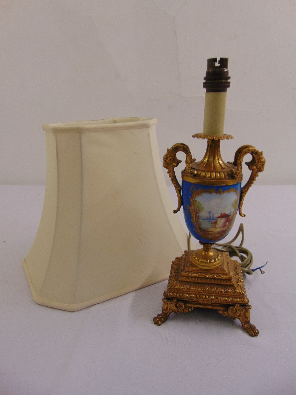 Lot 40 - A Sevres vase form gilt metal table lamp with scrolling side handles on raised square base with claw