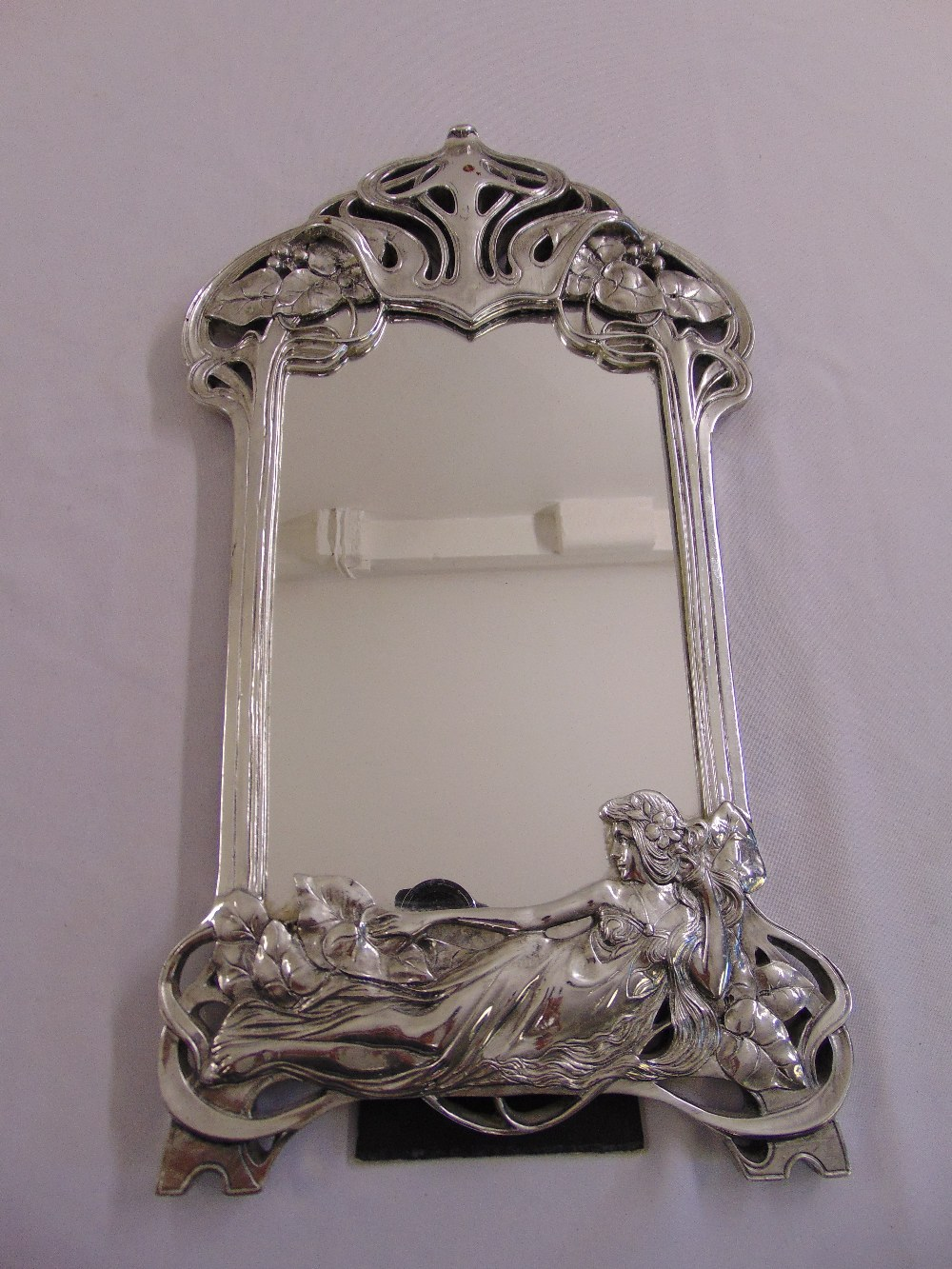 Lot 44 - A silvered Art Nouveau style table mirror shaped rectangular with stylised vegetation and a