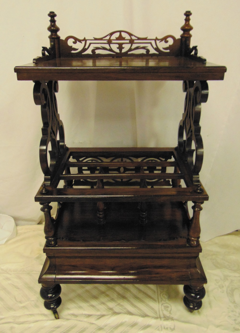 Lot 2 - A Victorian mahogany rectangular whatnot cum magazine rack with pierced scroll sides on four bun