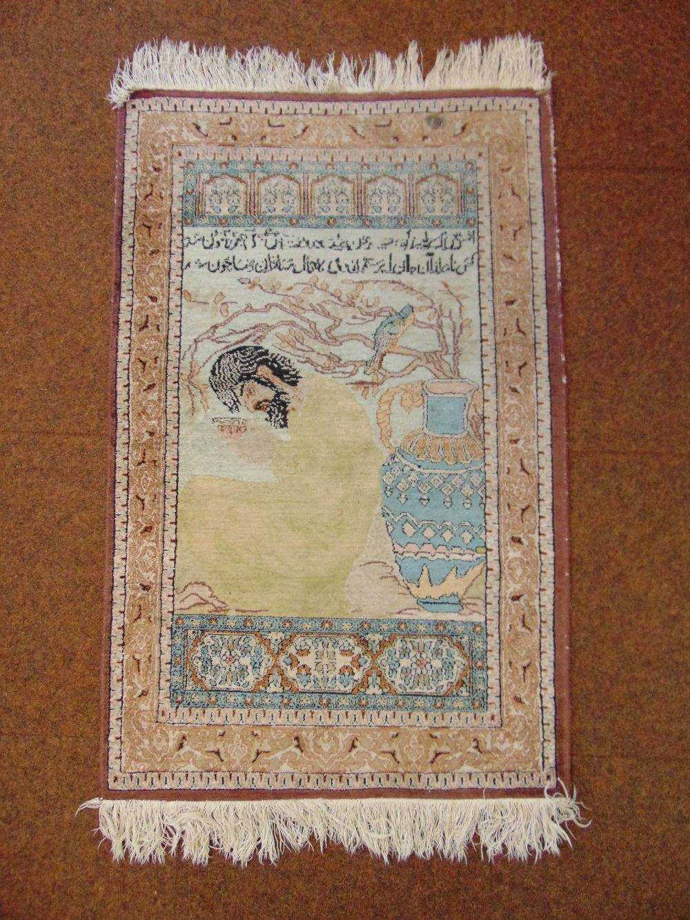 Lot 48 - A Persian carpet featuring a character drinking wine within a brown border with stylised geometric