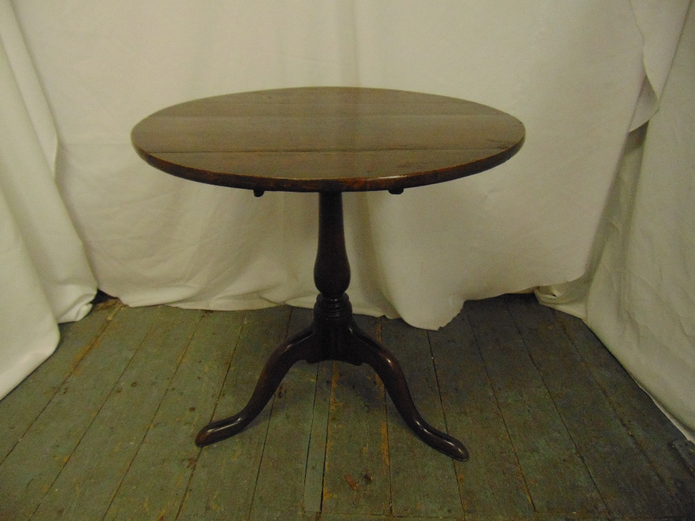 Lot 20 - A Georgian mahogany tilt top circular occasional table on three outswept legs