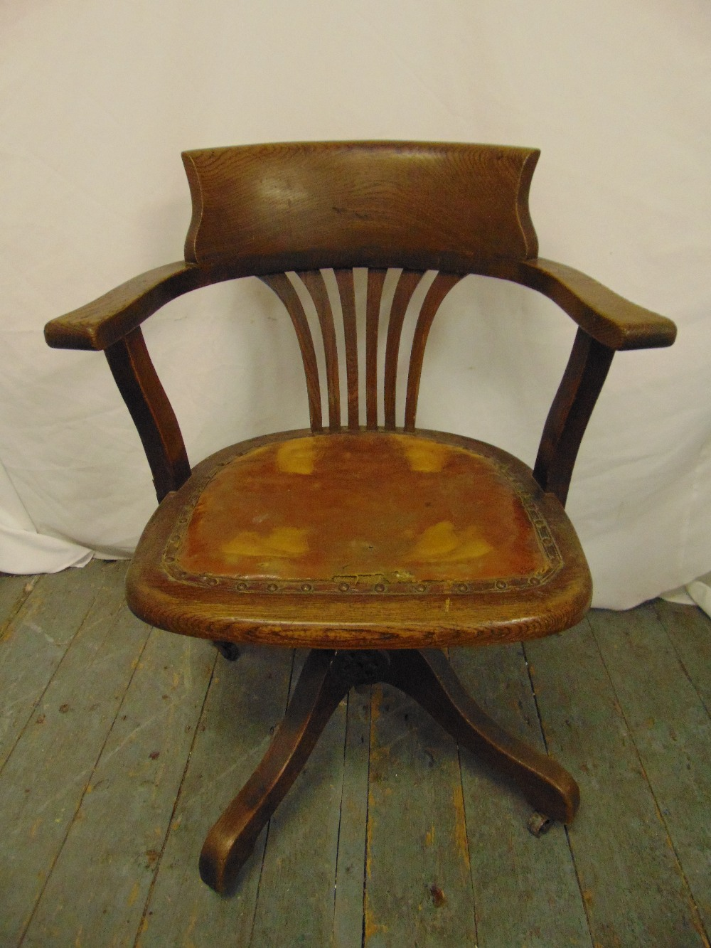 Lot 28 - An early 20th century oak captains chair with leather seat and original castors, label to base A M