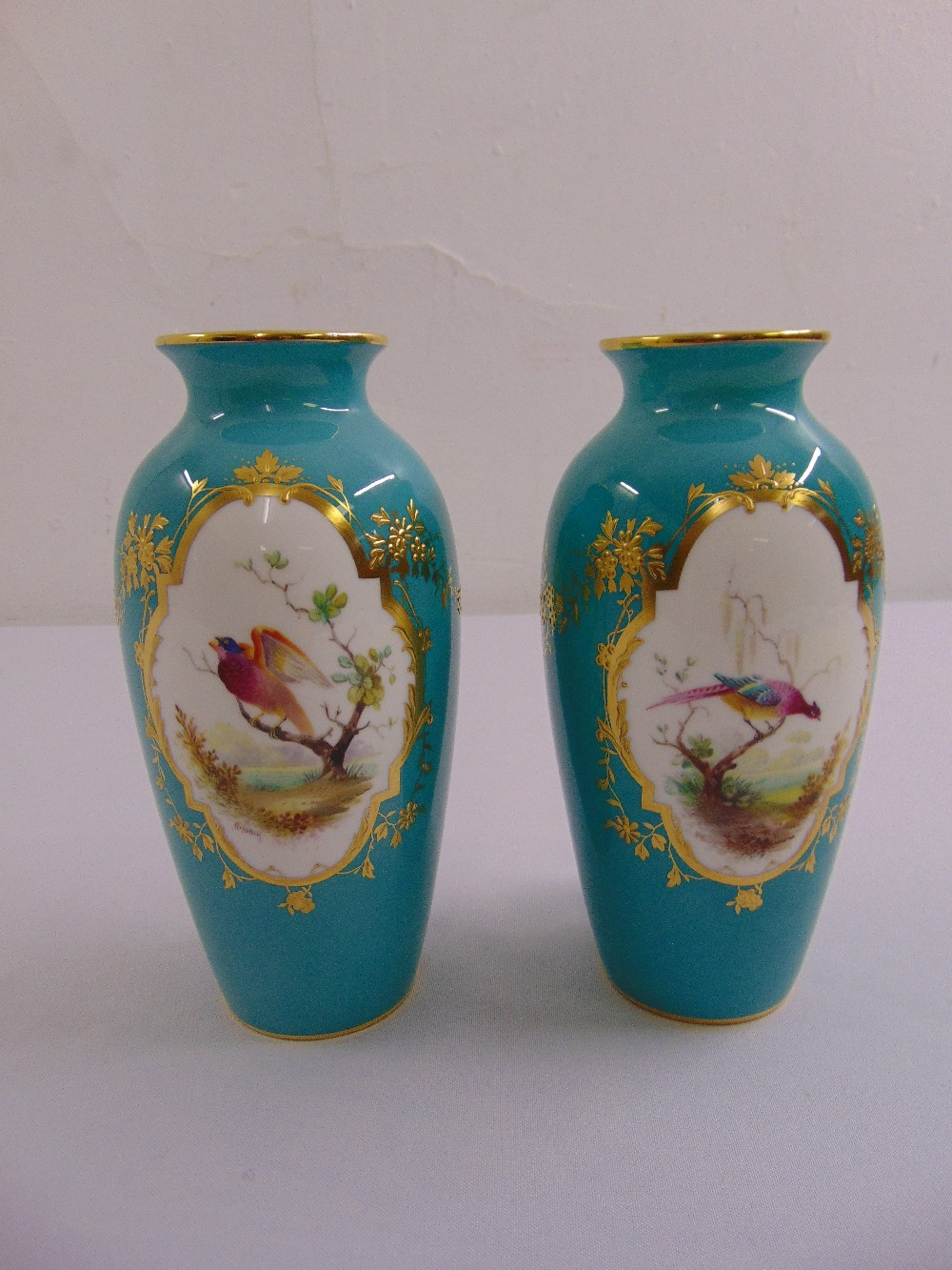 Lot 116 - A pair of early 20th century Minton baluster form vases decorated with stylised exotic birds,