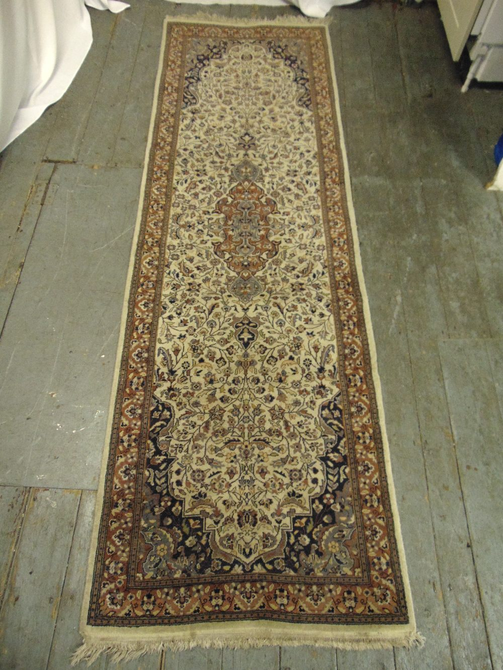 Lot 36 - A Persian wool runner brown ground and tan border with repeating floral pattern, 250 x 79cm