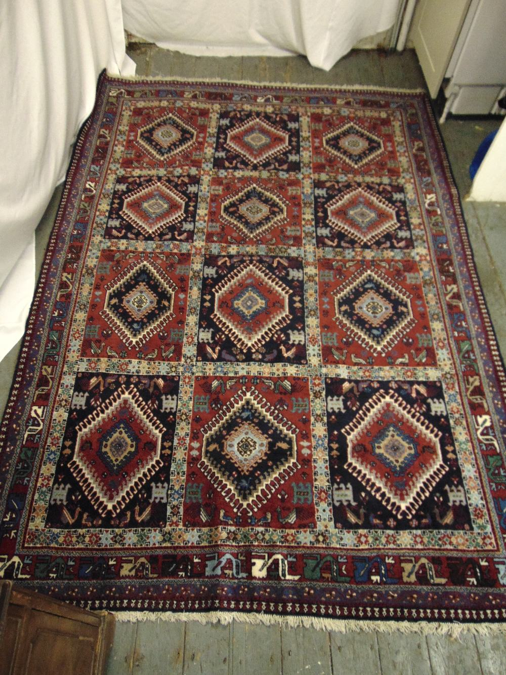 Lot 32 - A Persian Yalameh carpet, predominately brown, red and blue, formed as rows of diamond medallions