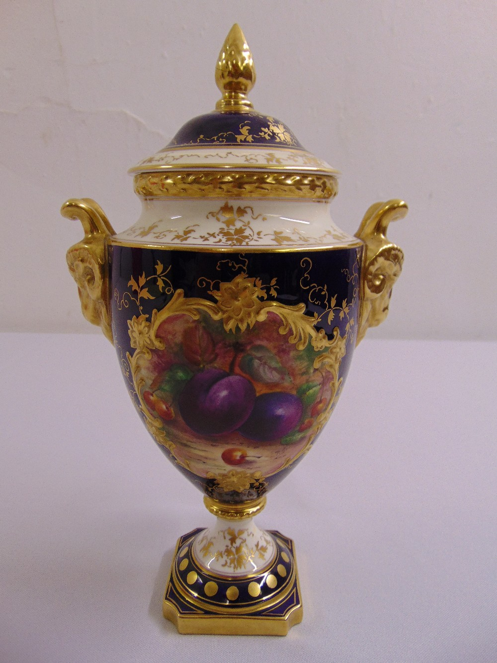 Lot 113 - A Coalport vase and cover with gilded rams mask side handles the sides painted with fruits, the