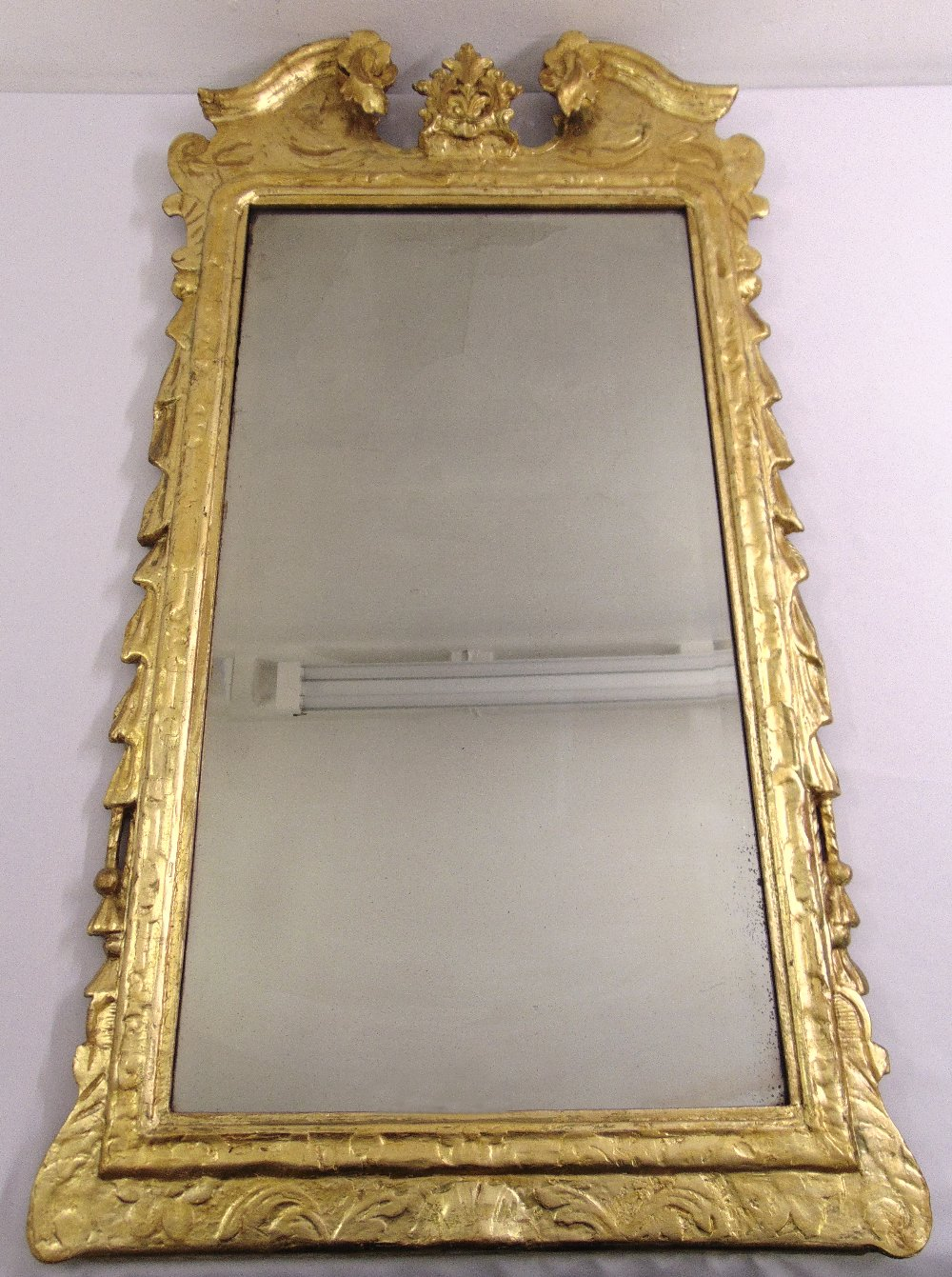 Lot 39 - A George I gilded gesso mirror with rectangular bevelled plate, the frame carved and moulded with
