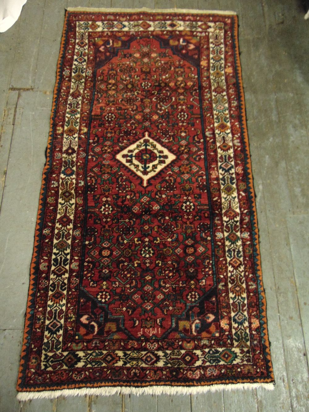 Lot 35 - Persian wool runner red ground with green and blue repeating pattern and cream border, 200 x 104cm