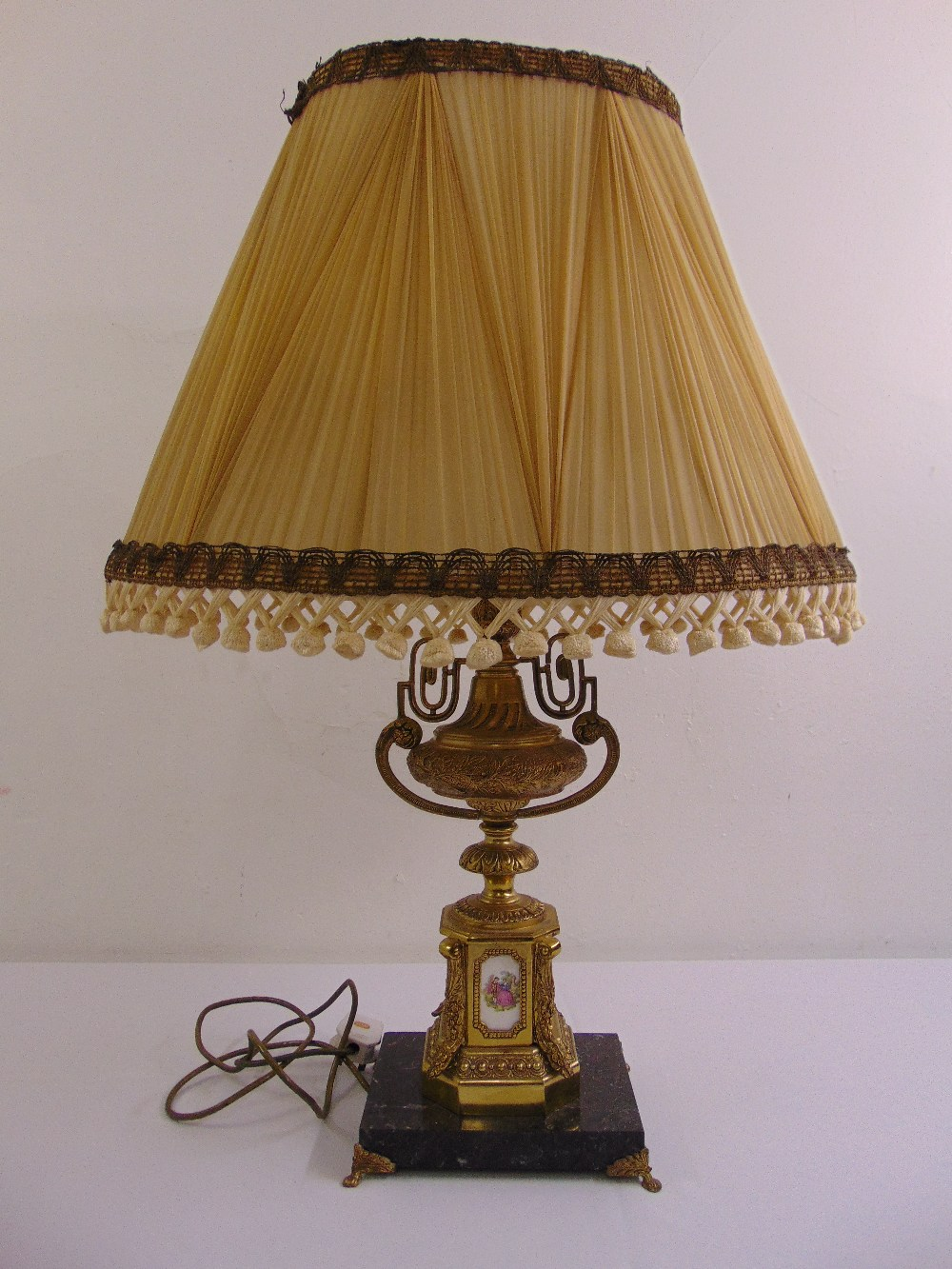 Lot 44 - A gilded metal table lamp on raised octagonal base with applied porcelain panels and silk shade
